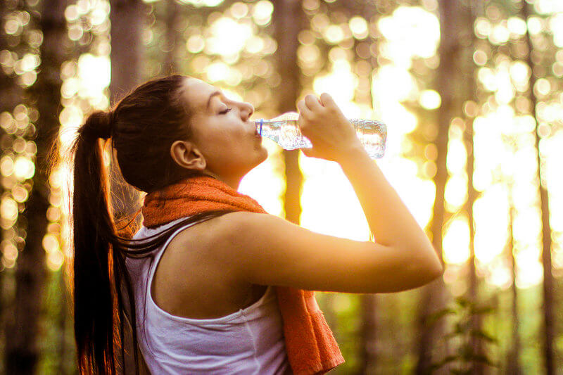 Young woman drinking out of her water bottle after her workout.