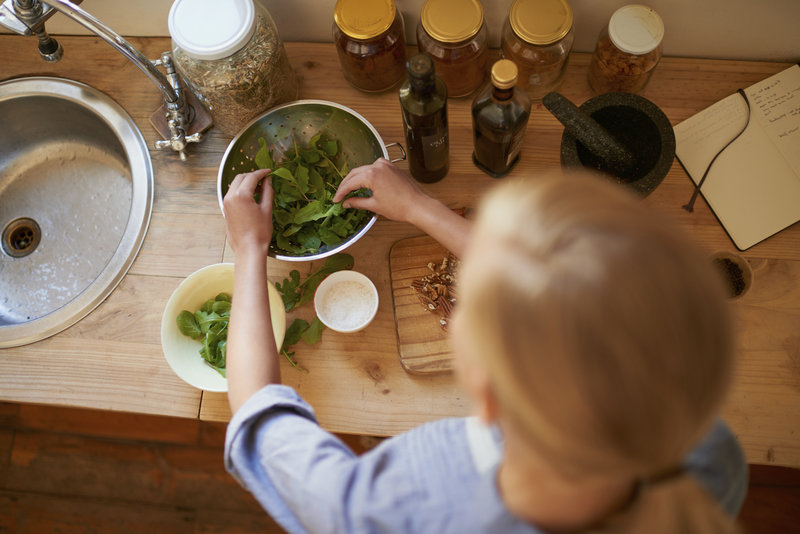 Woman preparing a healthy salad in the kitchen.