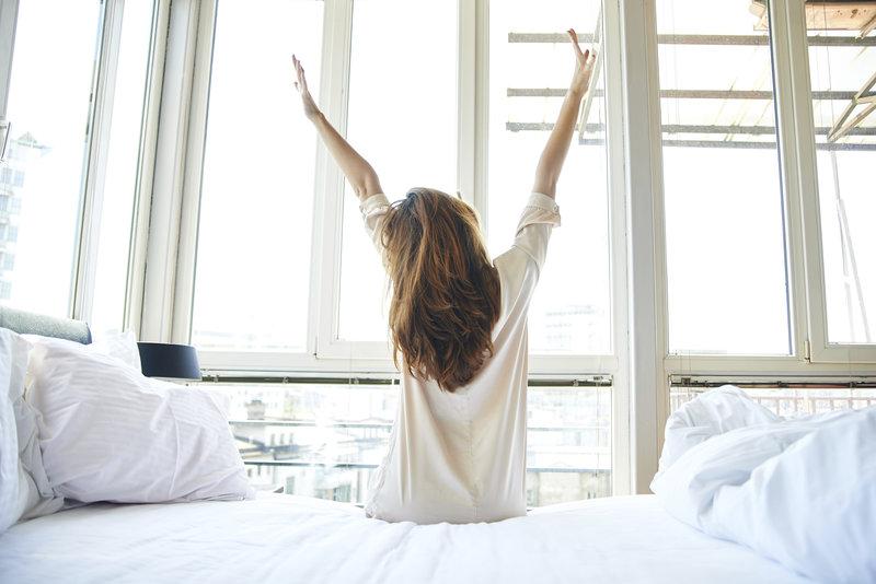 Jeune femme de dos qui s'étire avant de se lever de son lit.