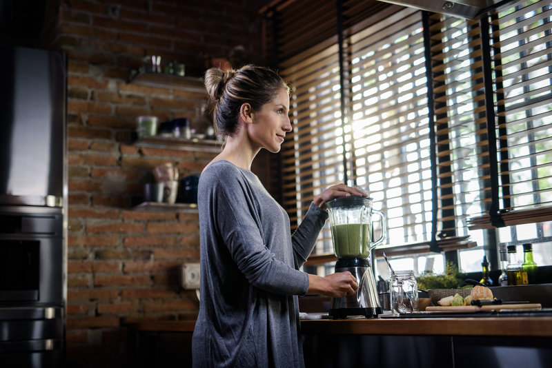 A woman is making a green smoothie in the kitchen