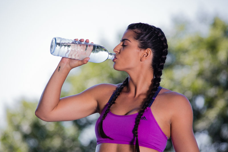 Young woman drinking out of her water bottle.