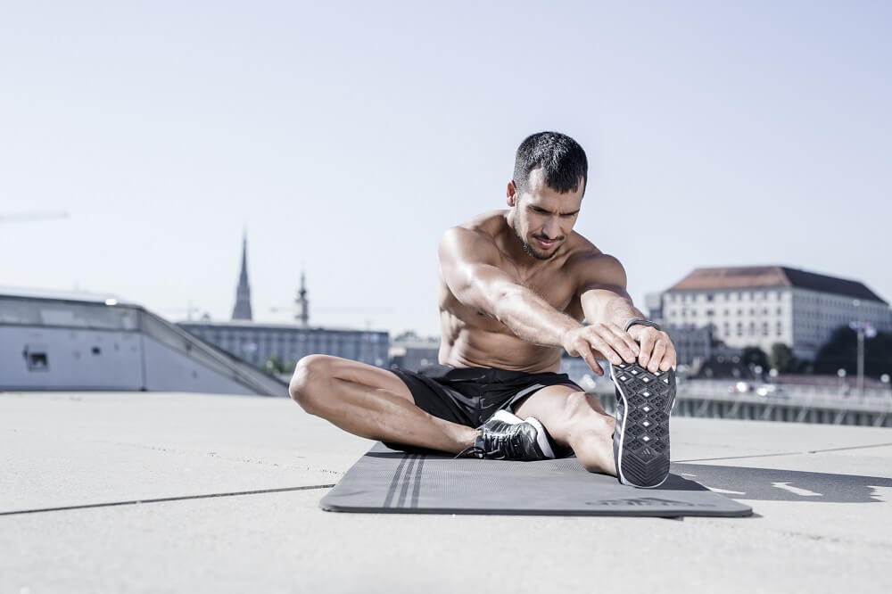 Uomo che fa stretching sul tetto di un edificio