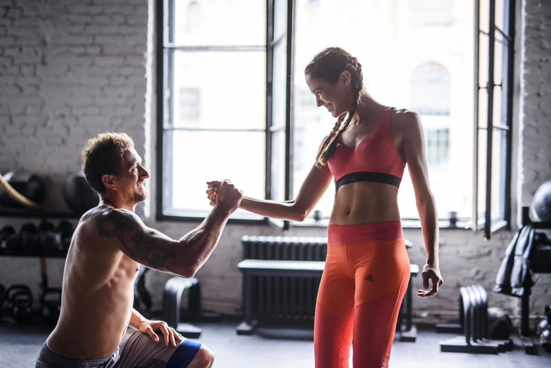 Couple doing a bodyweight workout together in the gym