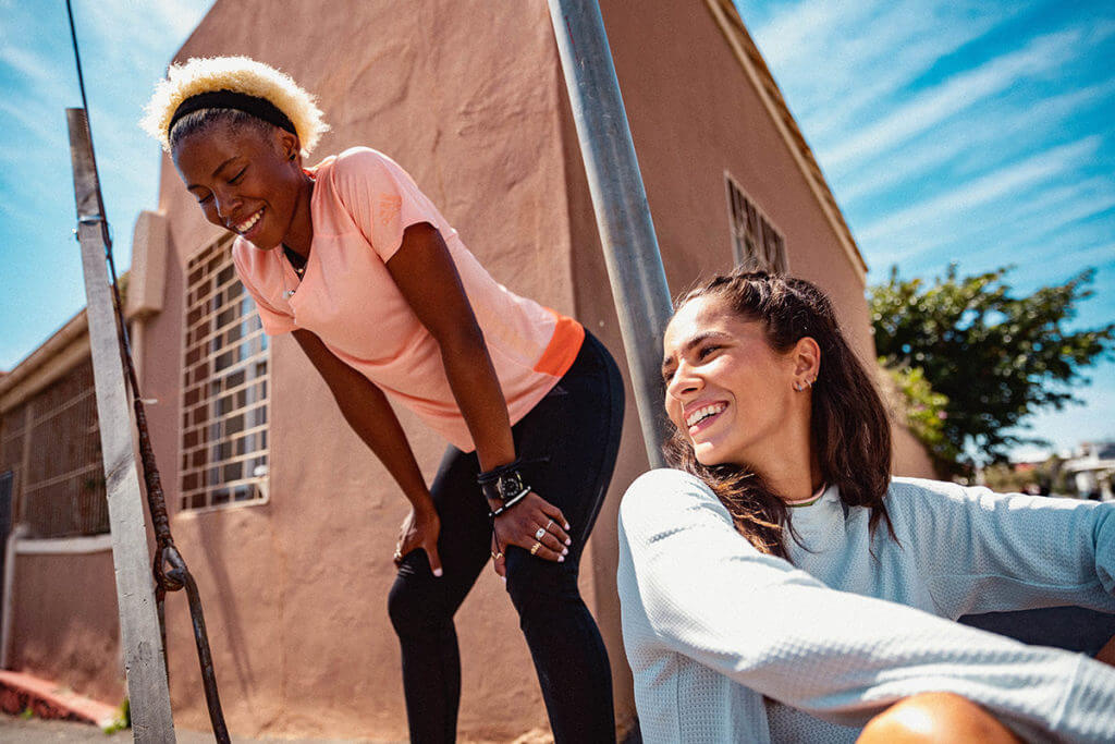 Due donne in abiti sportivi sorridono all'aperto perché hanno un'immagine del corpo positiva