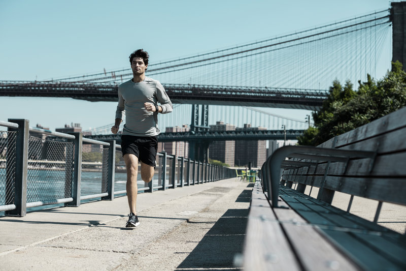 Young man running next to a river.