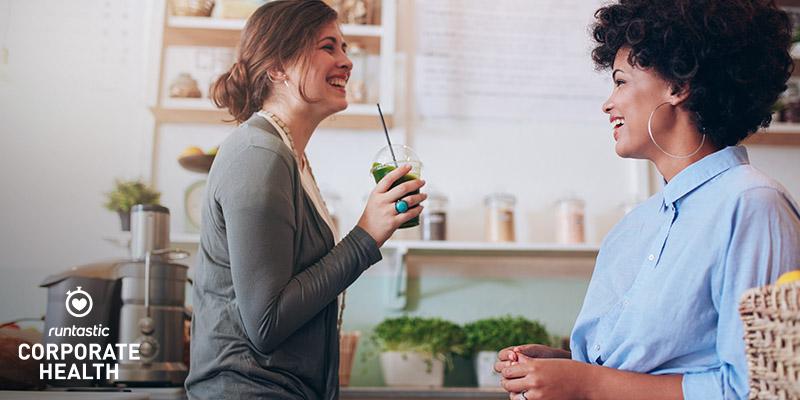 Zwei Freundinnen trinken einen Smoothie in der Kueche.