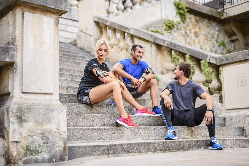Eine Frau und zwei Männer sitzen nach dem Lauf auf den Stiegen und unterhalten sich.