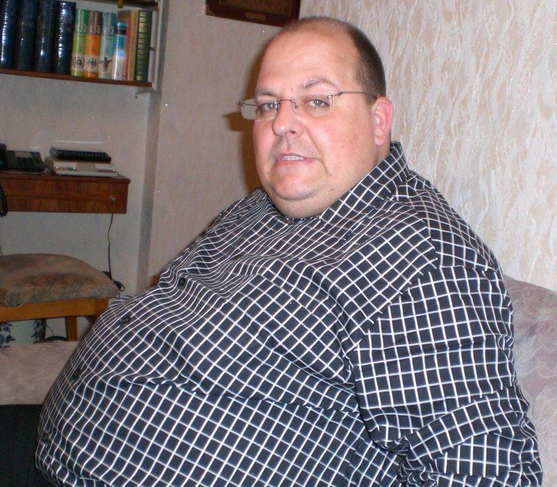 Ein übergewichtiger Mann blickt in die Kamera