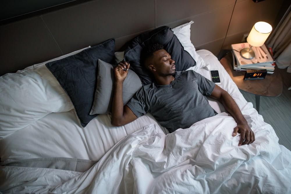 Ein afroamerikanischer Mann schläft im Bett