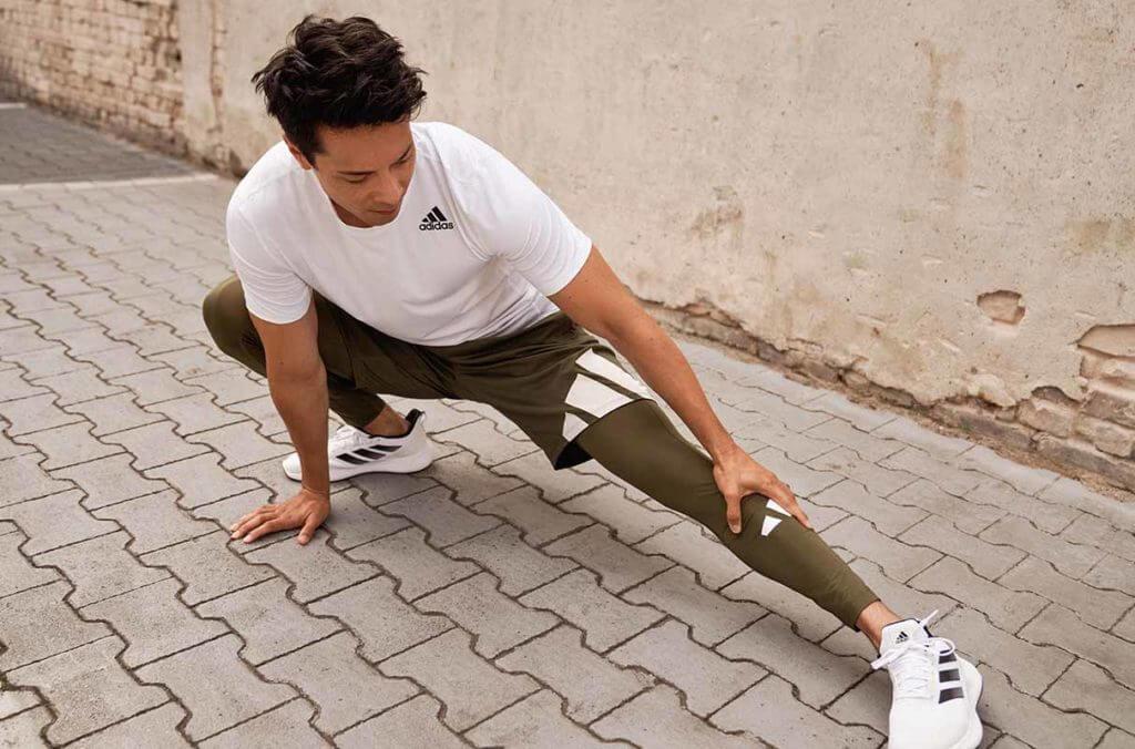 un uomo fa stretching prima della corsa