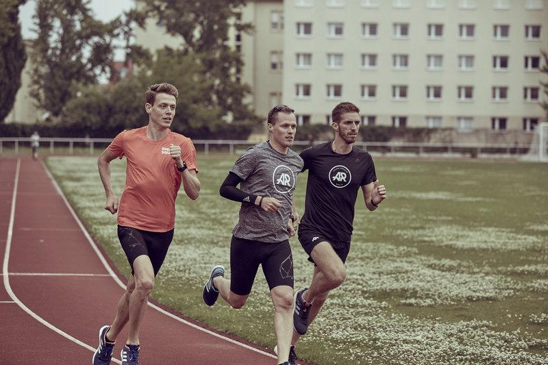 Drei Männer laufen auf der Rennbahn