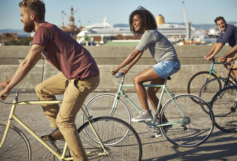 Mulher e homens andando de bicicleta em uma ponte