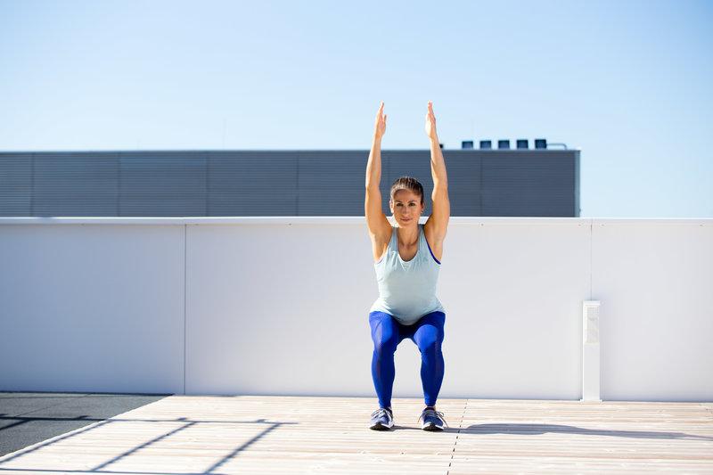 Woman doing an overhead squat assesment
