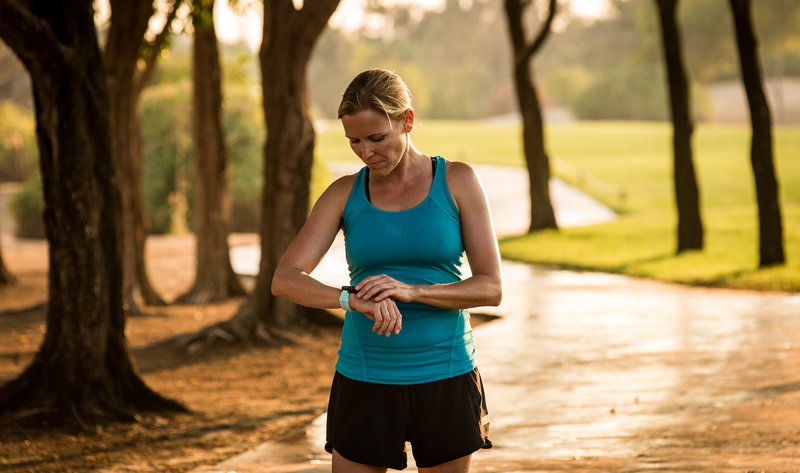 Woman checking her Garmin watch after a run outside
