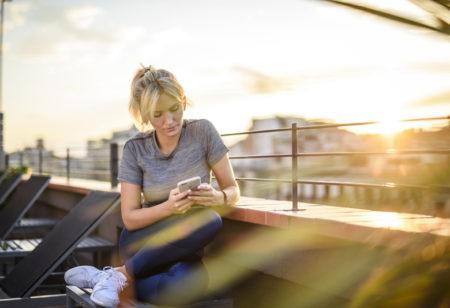 Eine Frau sieht im Freien auf ihr iPhone