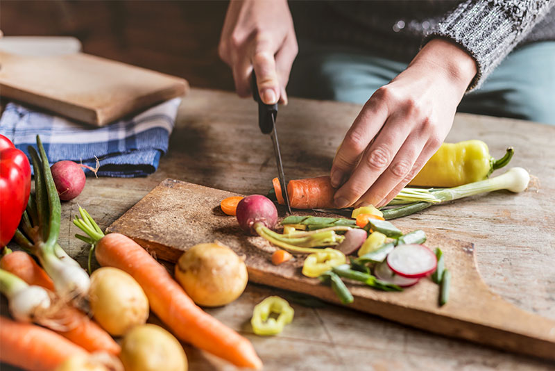 Someone cutting vegetables on a wooden plate
