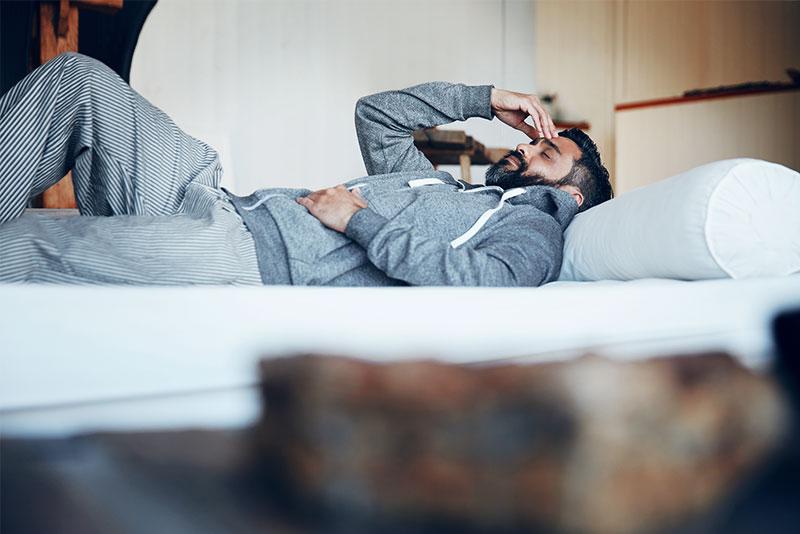 Un uomo sdraiato nel letto si tiene la testa con una mano