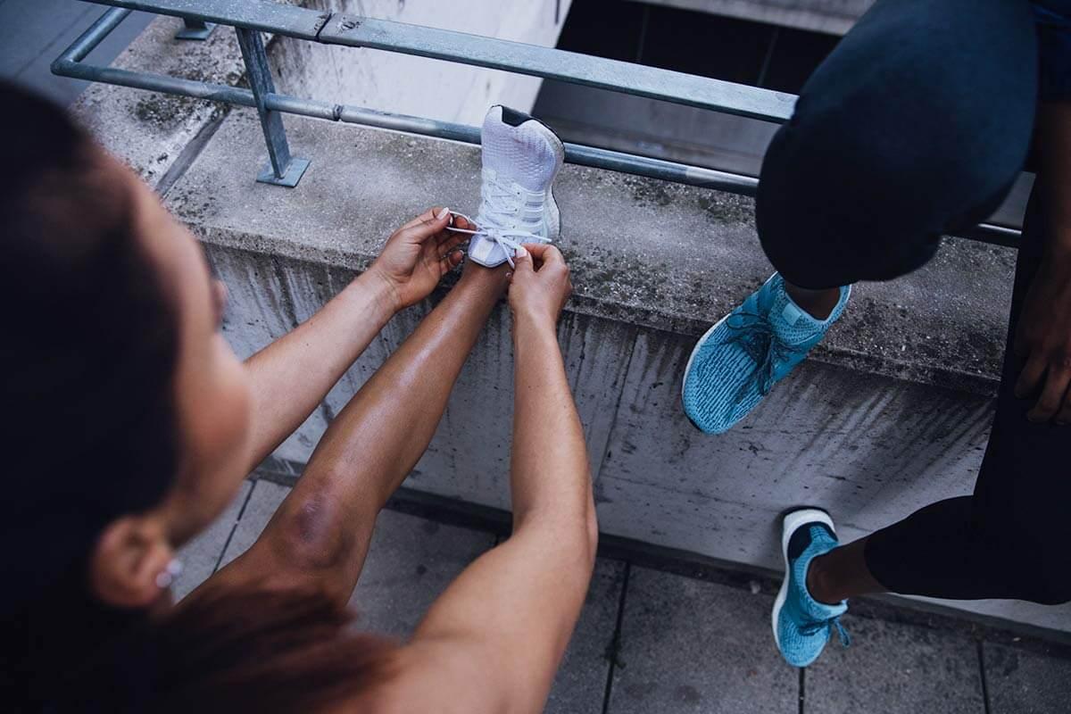 Eine Frau bindet sich die Laufschuhe