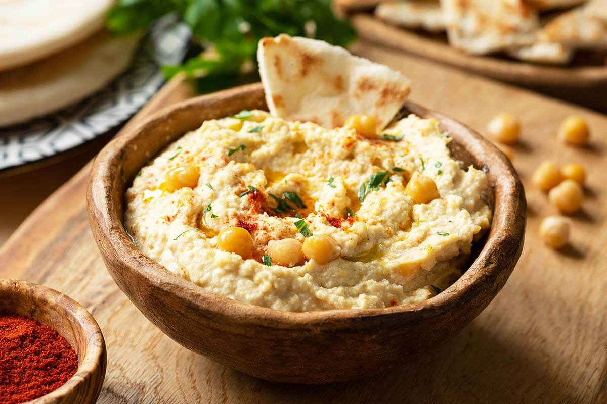 Pote contendo hummus e um pedaço de pão árabe