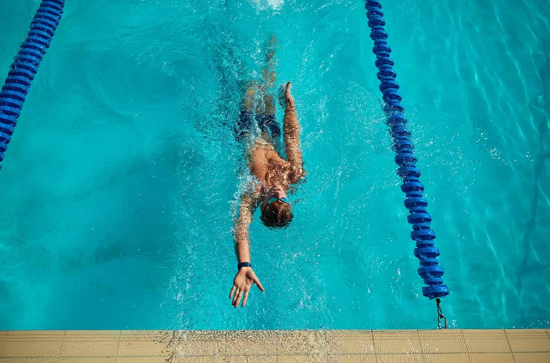 man swimming in lane