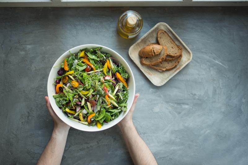 Eine große Schüssel Salat auf einem Tisch, daneben ein Teller mit Brot