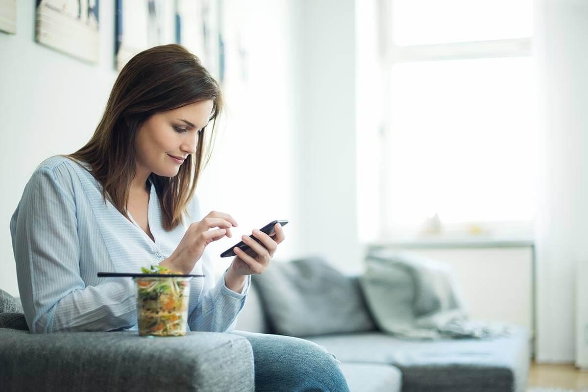 Mulher usando um aplicativo para acompanhar o peso corporal, pronta para comer uma salada.