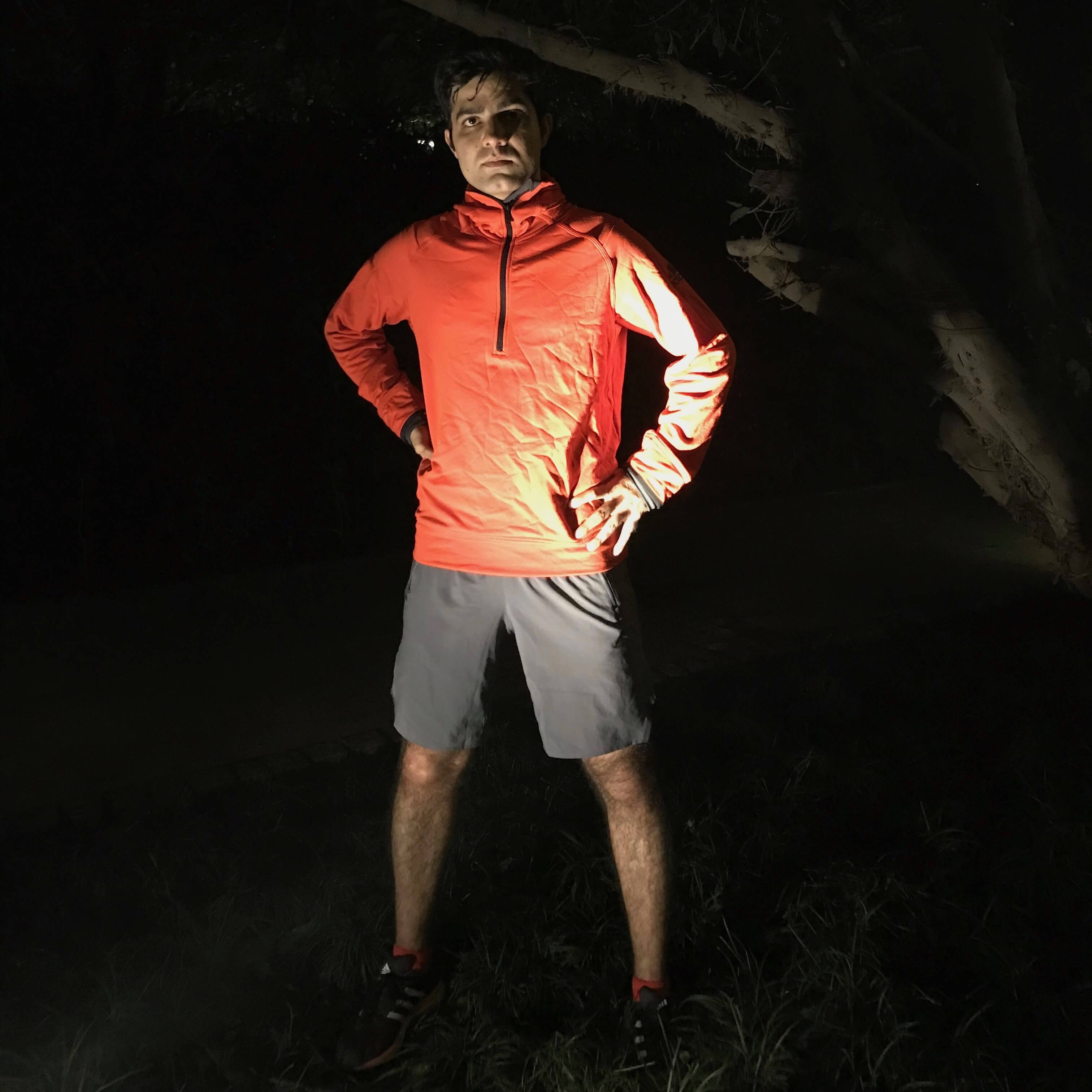 A man posing for the camera after his run at night