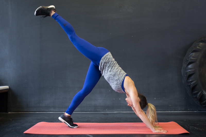 A woman is doing a single leg pike push-ups