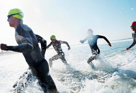 Eine Gruppe junger Leute läuft während einem Triathlon ins Wasser