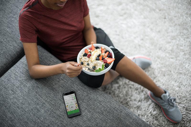 Une femme qui mange du muesli avec du yaourt et des fruits frais