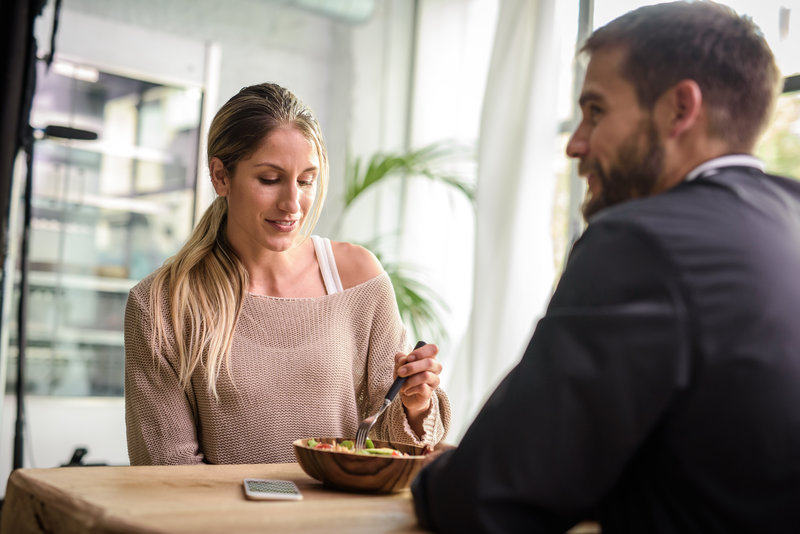 Zwei junge Menschen, ein Mann und eine Frau, beim Mittagessen mit einer Schüssel Salat
