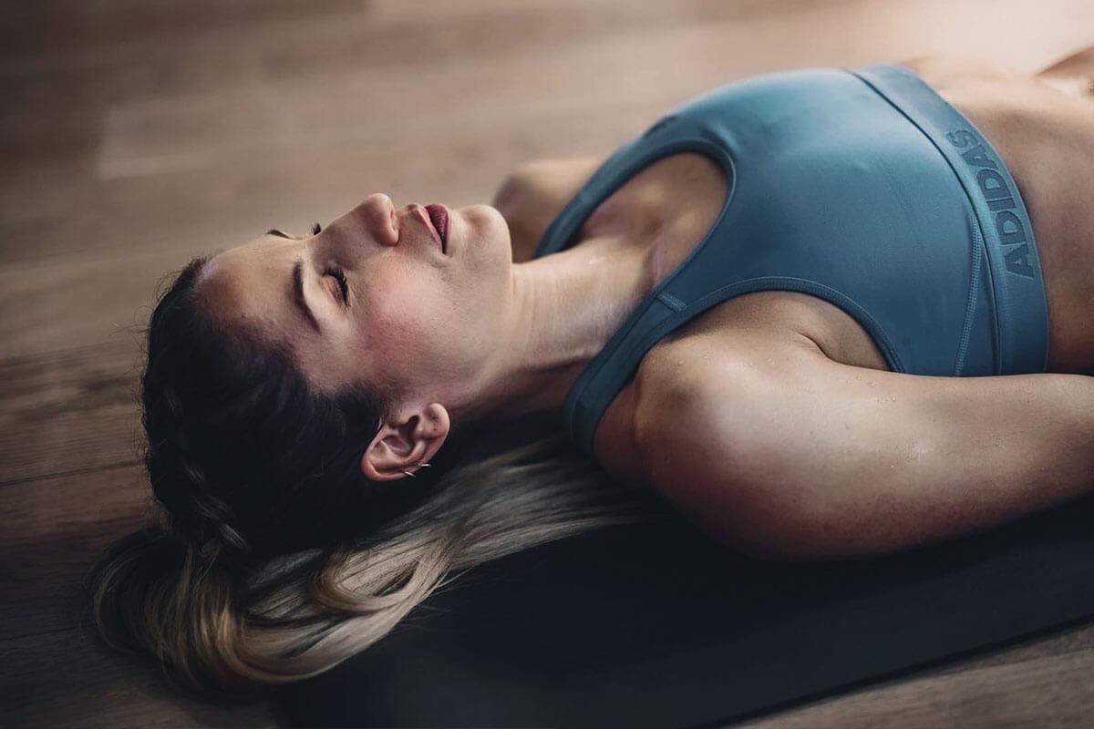 Mulher relaxando no tapete de yoga