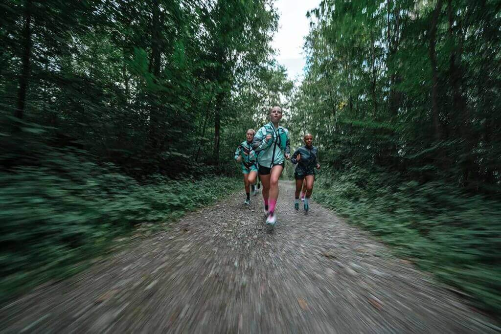 un gruppo di persone corre su una superficie sterrata in un bosco