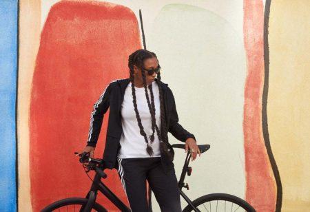 Pessoa com acessórios da adidas descansando ao lado de uma bicicleta