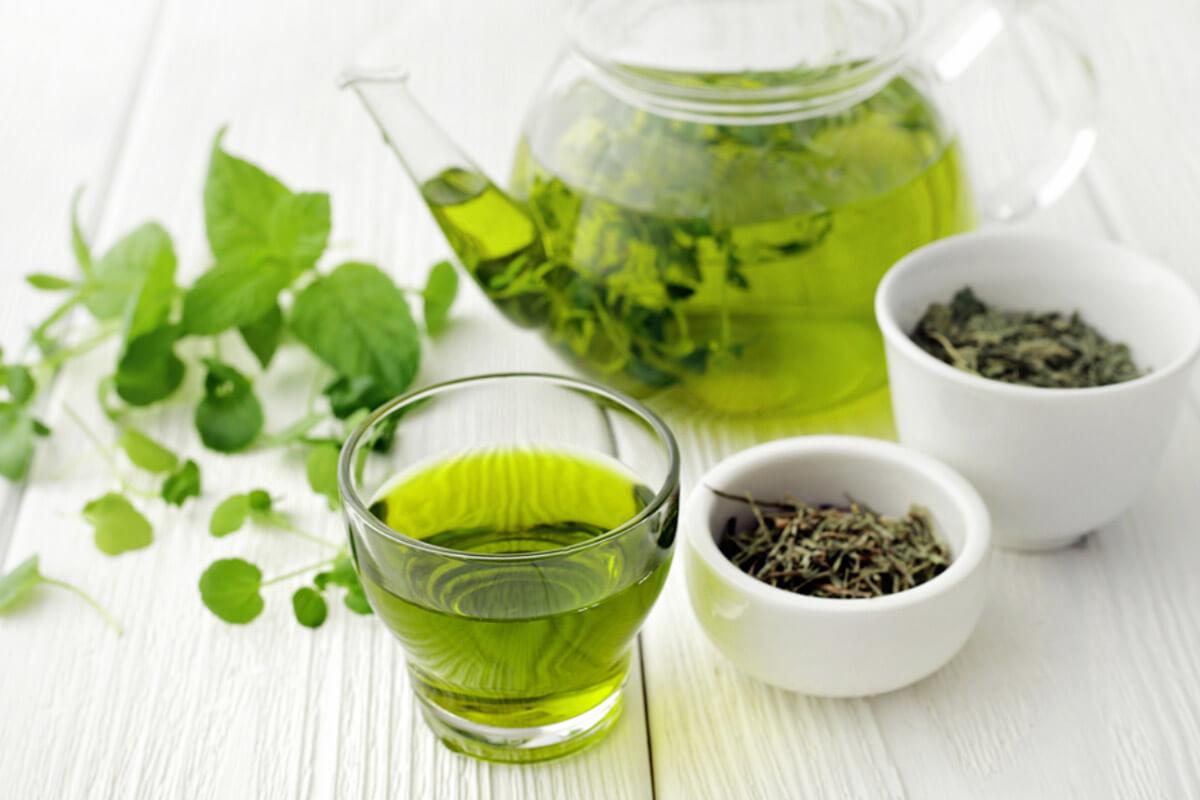bule contendo chá verde e um pouco da erva em potes sobre uma mesa