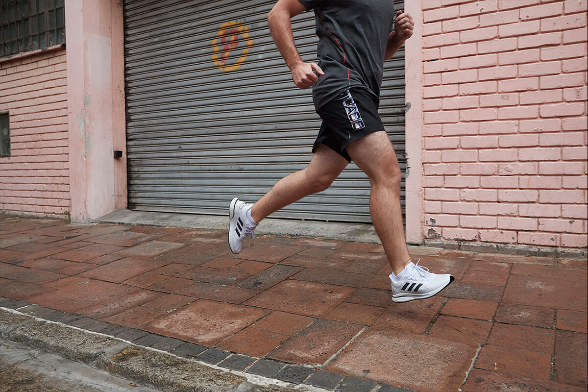 A running beginner is wearing adidas gear and running in the city