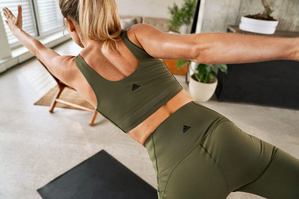 Woman working out at home - stretching on a sports mat