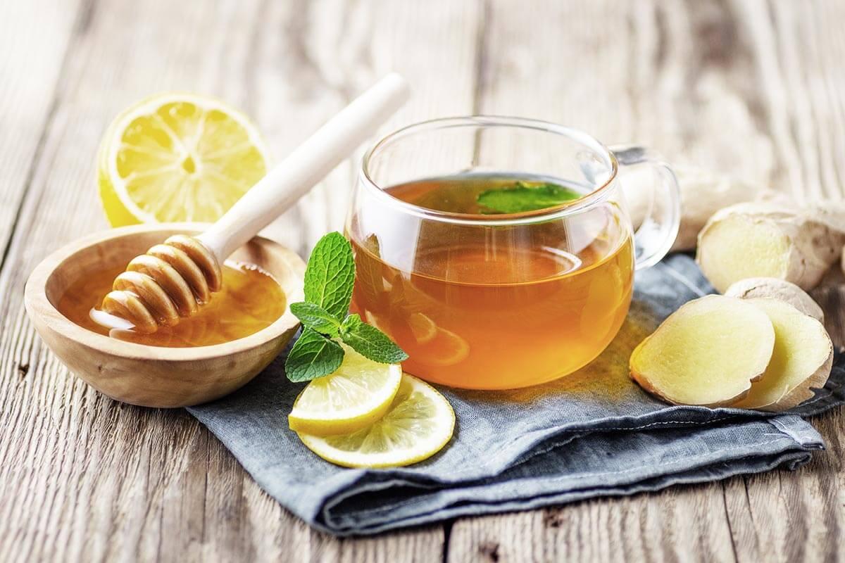 Bule contendo chá de hortelã. Sobre a mesa, um pote com mel, rodelas de limão e gengibre.