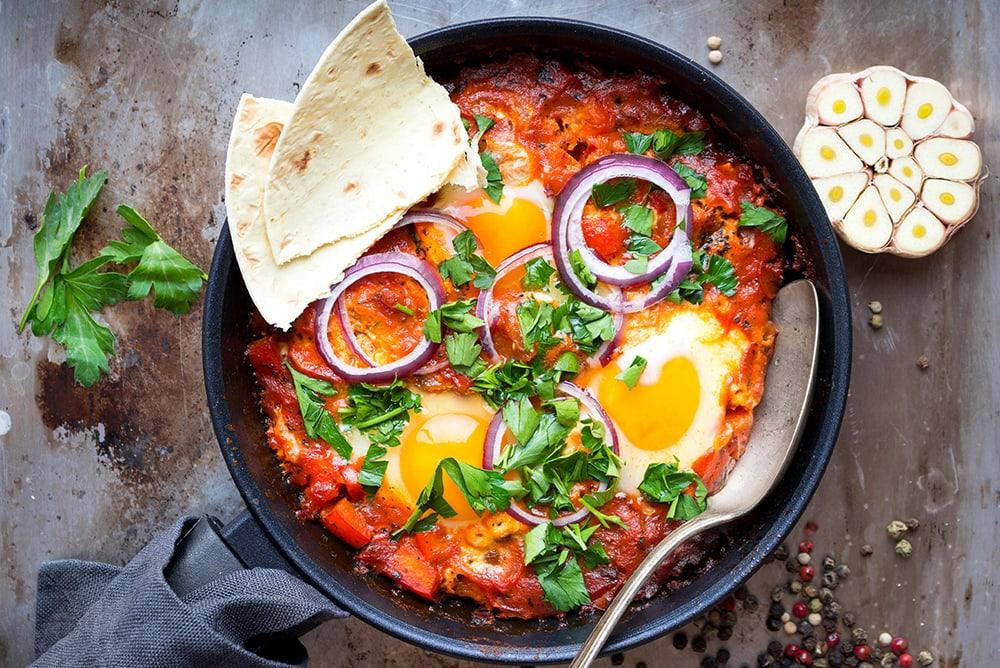 Frigideira com shakshuka, contendo ovos, ervas, anéis de cebola roxa e pão árabe