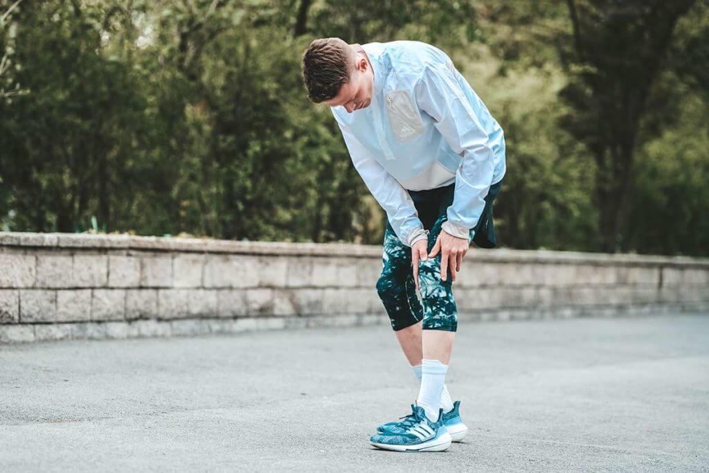Homem com dor no joelho durante a corrida causada por tendinite patelar (joelho de saltador)