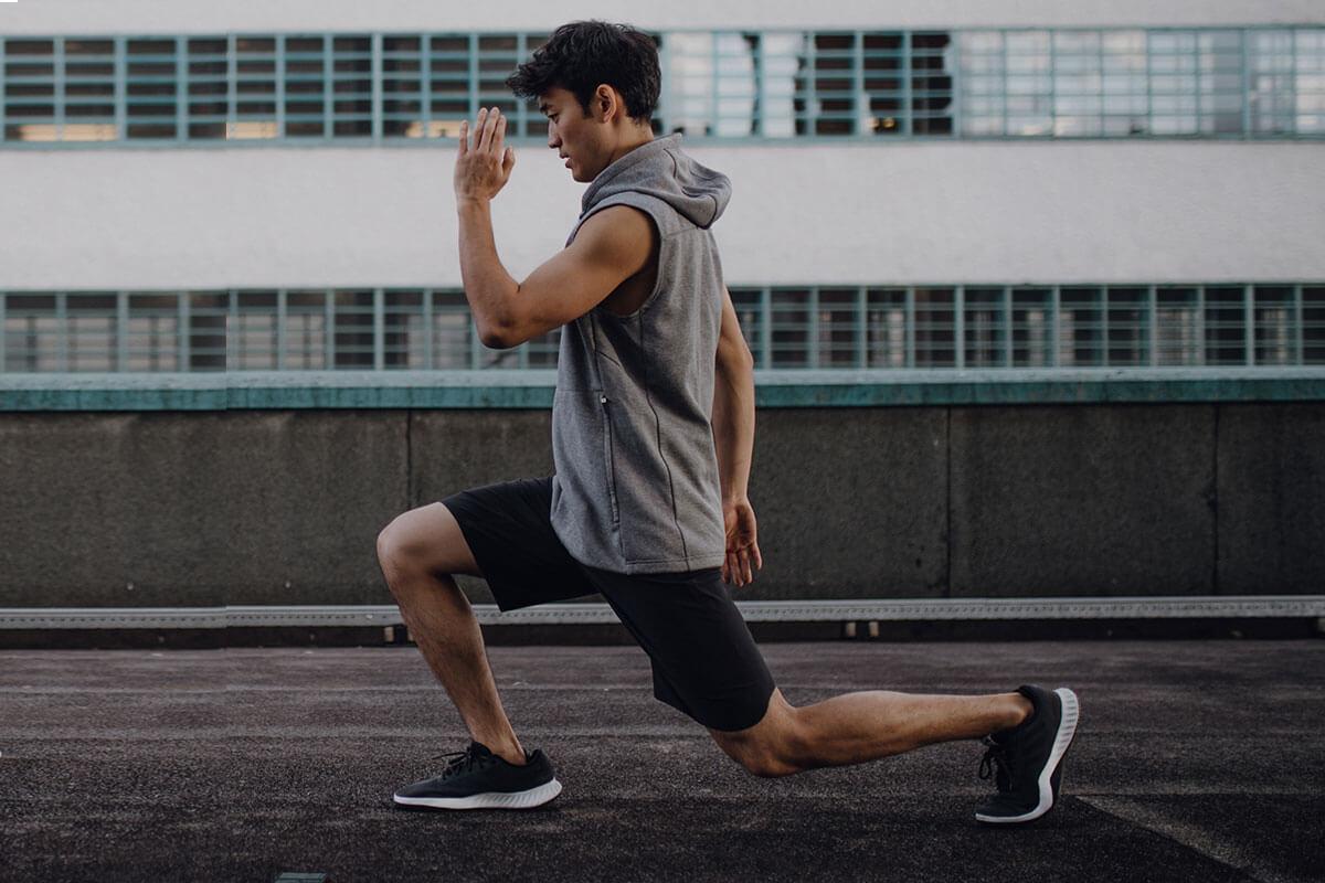 Ein junger Läufer macht Stretchingübungen nach dem Lauf