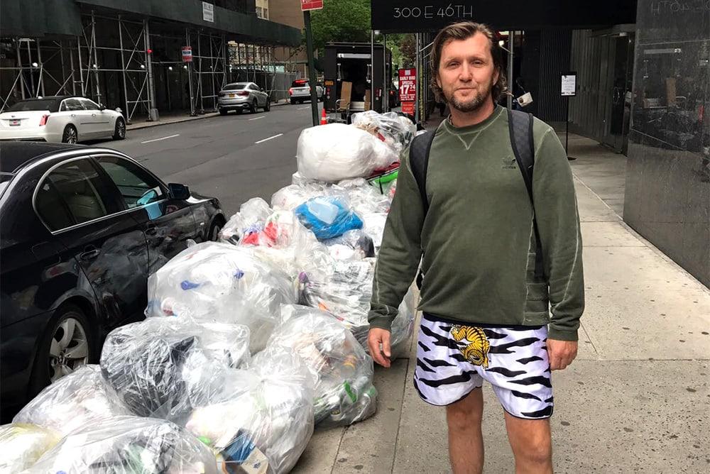 Mann, der nahe bei Stapel des Plastiks auf der Straße steht