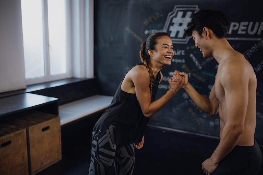 Zwei junge Menschen machen ein Workout und freuen sich über das abgeschlossene Training