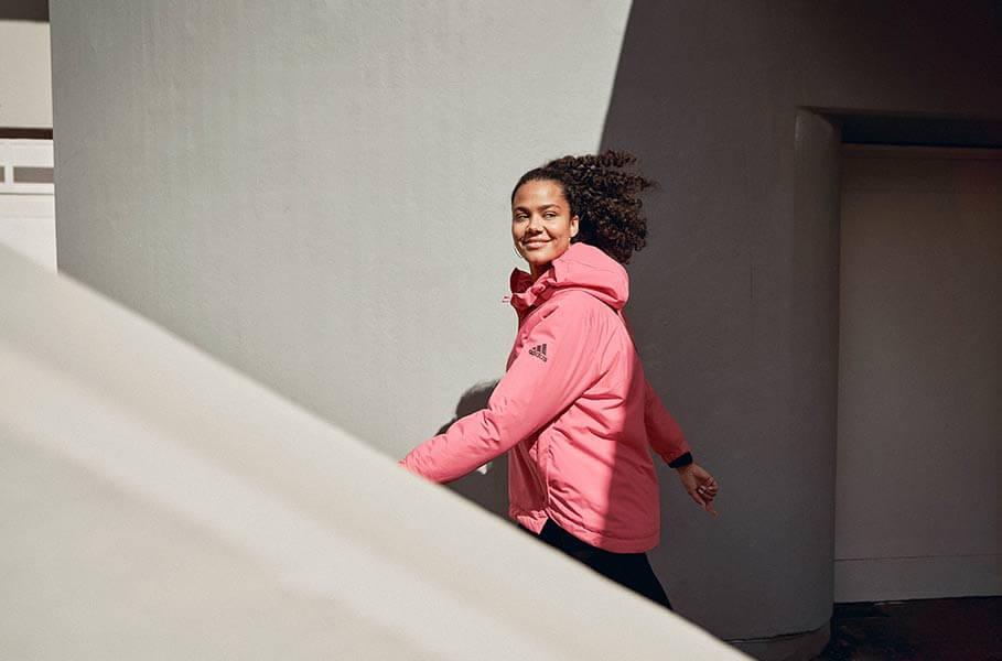 una persona cammina all'aperto con giacca adidas