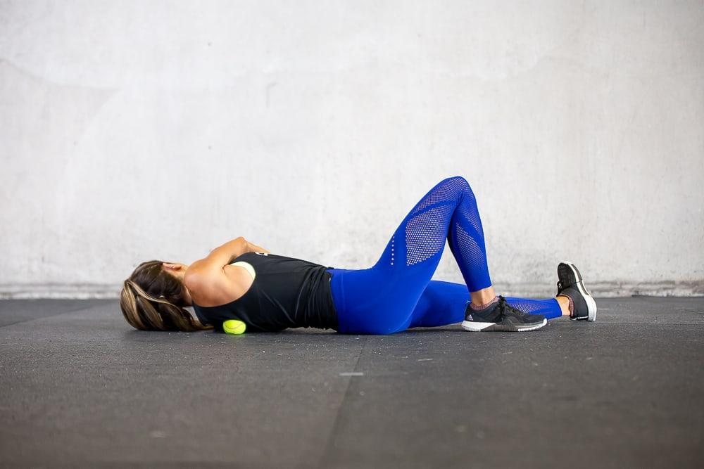 douleurs cervicales : une femme se masse le dos avec balle de tennis
