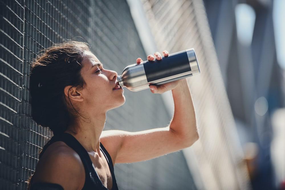 Frau trinkt Wasser nach einem Lauf