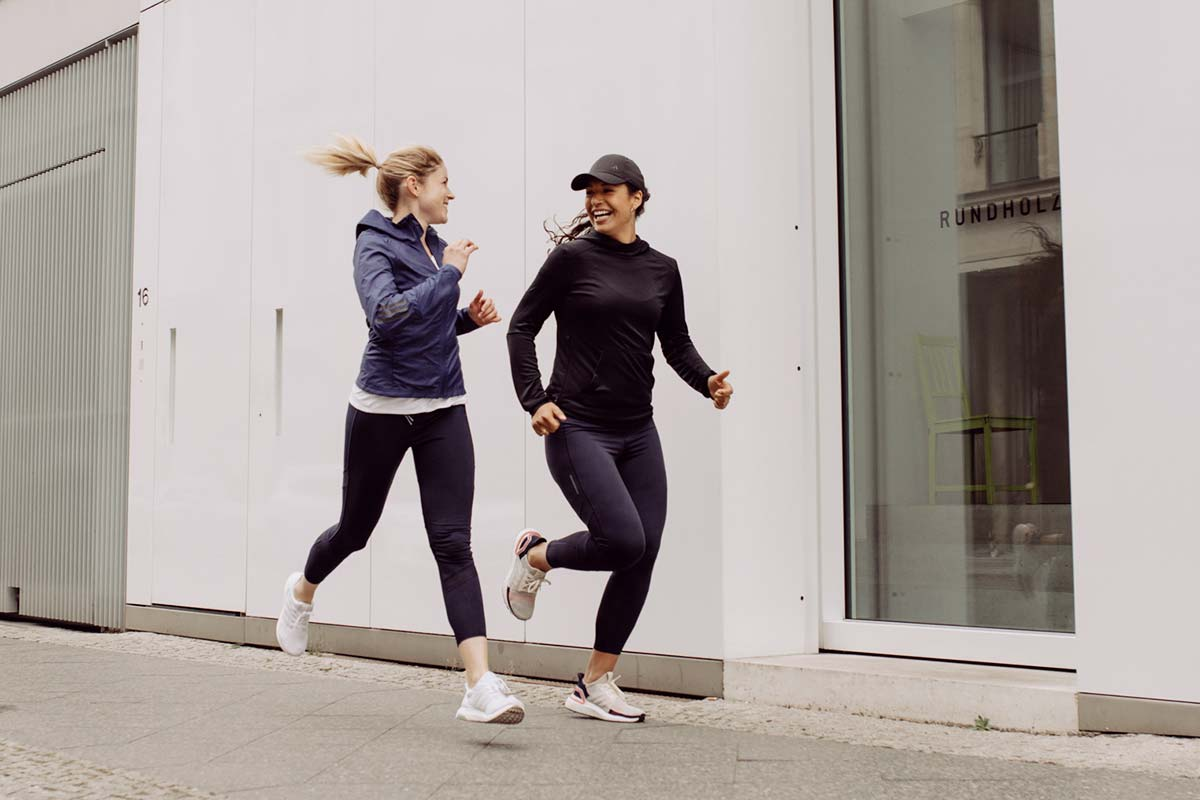 Two women laughing and running