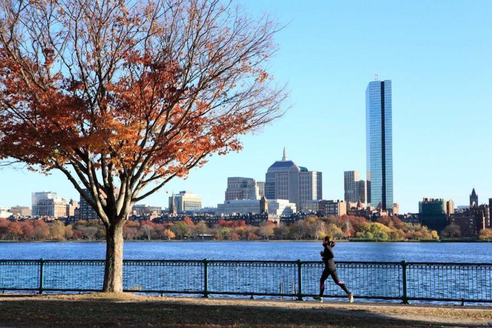 Mulher correndo à beira de um lago com prédios ao fundo
