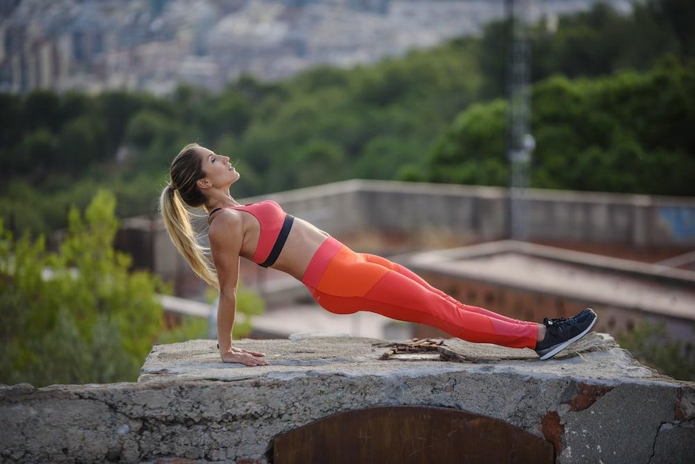 Mulher fazendo prancha invertida para ganhar massa muscular e fortalecer o core