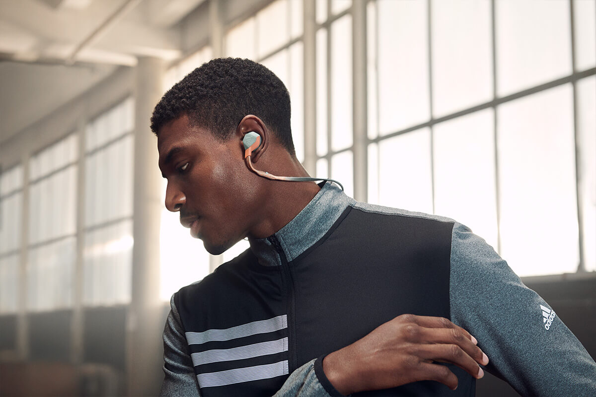 Black man listening to music with his adidas headphones